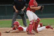 Mike Nielsen, Lansing High senior dives safely into home for Lansing's second run against Tonganoxie.