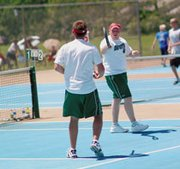 De Soto senior Dan Hoschouer looks to fellow senior Andy Edwards Saturday after Edwards scored a big point in the team's three-set loss to a Hayden pair in the state third-place game.