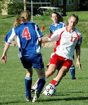 Lansing High senior defender Abby Hauver steals the ball from a Miege forward during Lansing's 1-0 victory Thursday.