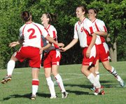 Lansing High junior Rachel Pride is congratulated by teammates Bianca Manago, Christine Cordes and Erin Griffen after Pride scored an early goal against Bishop Miege.