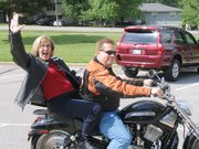 Retiring kindergarten teacher Jean Salmon waves while she takes a ride with Dr. Gary Courtney on his Harley-Davidson motorcycle.