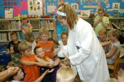 """Mad Scientist Laser Leah passes out bubbles to all the children. Leah made the bubbles as part of one of her experiments at the De Soto Library Friday at her Mad Science show """"Fire and Ice"""" where she taught children and adults basic science knowledge."""