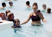 De Soto city lifeguard Rachel Day manages the coming and going Monday at the entrance to the pool's vortex feature. The Kansas State University student is earning money as a nanny as well as at the pool this summer.