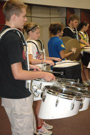 Chris Salavitch, front, practices with the drum line in the LHS band room. This year the drum line had help from a K-State student.