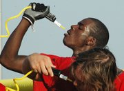 Kevin Johnson, Lansing High senior wide receiver, takes a water break during practice Monday.