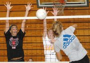 Lisa Angello, left, and Sara Logan attempt to block a spike by Brittney Lang during volleyball practice on Monday.