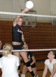 Lansing High junior Brittney Lang slams a kill during the Lions' Red-White Scrimmage on Thursday evening at LHS.