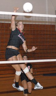 Lansing High sophomore Lisa Angello pounds a kill during the Lions' Red-White Scrimmage on Thursday evening at LHS.
