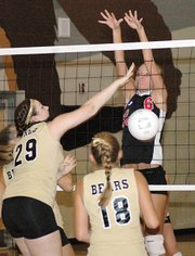 Lansing High junior Megan Grimm stuffs a spike by a Turner player.