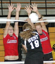 Lansing High's Julia Bates, left, and Brittney Lang combine for a block during Lansing's loss to Shawnee Mission West.