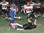 Lansing High senior Justin Smith trips up Santa Fe Trail wide receiver Dustin Hill.