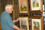 "Edwin Johnson hangs his watercolor Monday of the Sunflower towers at the De Soto Arts Council's ""Finding a Sense of Place"" show at Zimmerman Kill Creek Farm. A De Soto Rotary Club chili cookoff contest will join the show at the farm Saturday."