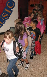 Students of Lansing Elementary School leave the gym Wednesday morning and head toward their classrooms to begin another day. The number of students enrolled at the elementary school dropped by two this year, but the number of students in the entire district increased by 99.