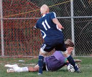Lansing High goalkeeper Ethan Alexander takes the ball off the foot of Mill Valley's Spencer Nash during Mill Valley's 4-0 victory.