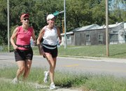 Vickie Kelly, left, and Tera Cameron run along Pennsylvania Street in an 18-mile run as part of their training for the New York City Marathon on Nov. 4. The two have been friends for 15 years and done many physical activities together such as mini-marathons, triathlons and biking across Kansas.