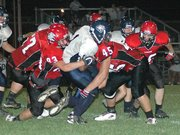 Lansing High's Ryan Delich (83) and Brad Terron (45) tackle Mill Valley junior running back Nick Woods.