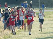 Lansing High sophomore Brandon Craig charges up the home stretch at the Kaw Valley League championships as teammate and girls runner-up Lauren Jaqua cheers him on. Craig was the varsity boys' individual league champion.
