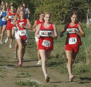 Lansing High sophomores Sarah Nielsen, left, and Melanie Pilkington race side-by-side early in the KVL championship varsity race. Nielsen finished fourth and Pilkington seventh as the LHS girls won the team title.