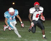 Lansing High running back Chris Hill, at a rare moment Friday night, finds room to run against Shawnee Heights.