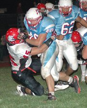 Lansing High senior linebacker Brad Terron drags down Shawnee Heights running back Austin Flohrschutz.