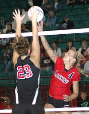 Lansing High senior Sara Logan tips the ball over an Emporia blocker at the Class 5A state volleyball tournament.
