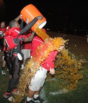 Lansing High senior wide receiver Kevin Johnson pours the Gatorade bucket on LHS head coach Bill Pekarek as the final seconds tick off the clock. LHS beat Schlagle, 41-14, and won the Class 5A District 1 championship.