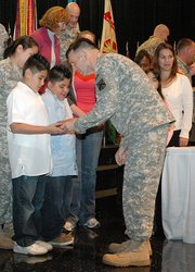 Lt. Gen. William Caldwell IV hands two Eisenhower Elementary students, Mauricio Hernandez (left), 10, and Diego Hernandez, 9, a commemorative medal following the Army Family Covenant signing held at Bradley Elementary School on Thursday, Nov. 8. The signing was to recognize the commitment and increasing sacrifices that Army families are making every day.
