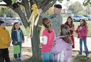 Maj. David Steele cuts down a yellow ribbon at Lansing Elementary School Thursday, Nov. 8, that was hung for him when he was deployed to Iraq in August 2006. Steele was joined by his daughters Alysabeth, 10, and Emily, 7, and the members of Emily's second-grade class.