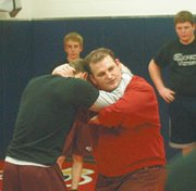 Eudora coach BIll DeWitt goes over a move with one of his wrestlers Wednesday. The team opens its season Thursday.