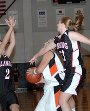 Bonner Springs' Kelsey Stanbrough tries to put up a shot as Lansing's Amanda Darrow, left, and Amy Briggs, right, defend.