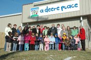 Debbie Deere, owner of A Deere Place, cuts the ribbon for the ceremonial opening of the new preschool at 1104 Industrial Street in the Lansing Business Center off Gilman Road. A Deere Place offers all-day and half-day care for children ages three to six and before and after school care for Lansing Elementary and Intermediate School students. Standing to Deere's left is Lansing Mayor Kenneth Bernard and to her right is Lansing Chamber of Commerce president Greg Madsen and her husband Kyle Deere. Some of the students and staff of the center, which moved to the new location on Nov. 1, also joined her for the ribbon cutting.