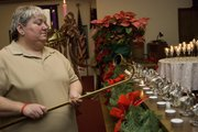 Sue Hollingsworth lights a candle during the 2007 Blue Christmas service at the McLouth United Methodist Church, to honor the memory of her uncle, Harold Roland, a retired Oklahoma highway patrolman, who died last November.  This year was the third year the church provided this service for grieving church members during the holidays.