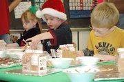 Destiny Hagen, 5, left, Conner Fouquet, 6, center, and Logan Hope, 5, of Andrea Rothmeyer's kindergarten class at Lansing Elementary decorate gingerbread house Friday, Dec. 21. The project completed a unit that used the gingerbread man theme to teach fundamental lessons.