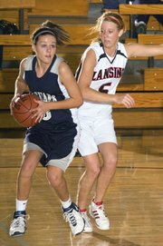 Mill Valley sophomore Whitney Hartman (left) looks for an open lane against the Lansing defense pressure from Brittney Lang.