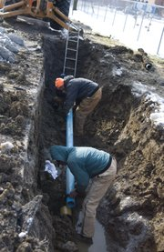 Patrick Bartlett, back, helps McLouth Superintendent Carl Chalfant install the new 4 inch PVC pipe to replace the pipe that burst yesterday morning. The two men along with Gary Tullis worked in below freezing temperatures to restore water by 11 a.m.