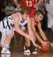 Caleb Smith (left) and Keith Wentz-Hall fight for a loose ball Friday as Mill Valley defeated Tonganoxie 57-40.