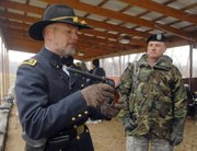 Kendall Gott, left, senior historian at Fort Leavenworth, shows Maj. Brett Clark an 1873 Colt and tells him how the gun works. ROTC instructors and military students were on hand Thursday, Jan. 10, at Fort Leavenworth's firing range to learn about several 19th-century weapons that had been used by U.S. armed forces.