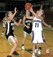 Baldwin High School junior Tracie Weege (No. 11) attempts a shot between a trio of Paola players Friday night. Weege scored 10 points to help the Bulldogs beat the Panthers 64-55.