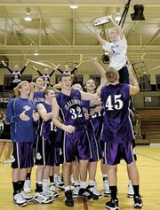 Baldwin High School junior Clad Kueffer (No. 45) lifts Adam Carlson, 9 years old, into the air after the Bulldogs won their home tournament Saturday. Carlson is the nephew of BHS coach Eric Toot.