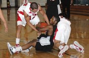 Lansing High's Stephen Didde, left, and Curtis Beall, right, tangle for a loose ball with Bonner Springs' Ariel Adger.