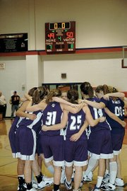 Members of the Baldwin High School girls' basketball team celebrate their third-place finish with their tradition of huddling and placing their left feet in the middle of the circle. The Bulldogs beat Kansas City Piper 50-49 Saturday night to finish third in the Top Gun Tournament.