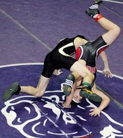 Lansing High freshman Spencer Blew tangles with Paola's Mitch Mosely during the third-place match at 125 pounds at the Baldwin Invitational. Blew won by major decision, 18-6.