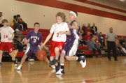 Warriors guard Conner Kietzmann attempts to drive the lane against Piper's defense on Jan. 22.