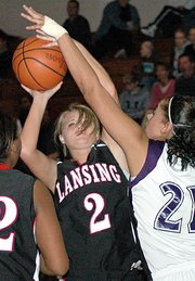 Amanda Darrow, Lansing High senior, is fouled by Piper's J.C. Carroll while putting up a shot Tuesday night. Darrow scored eight points during Lansing's 60-49 victory.