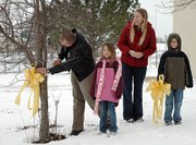 Maj. Jerry Diamond cuts down a yellow ribbon hung by his two children, Allison, 6, and Alex, 8, at Lansing Elementary School during his deployment to Iraq. Diamond recently returned to his children and wife Victoria, second from right, after being deployed in November 2006.