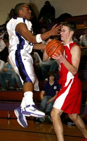 Lansing High junior Clayton Hall fends off a defender during Lansing's loss at Piper.