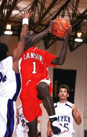 Lansing High senior Kevin Johnson goes up for a layup during Lansing's loss to Piper.