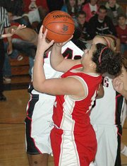 Tonganoxie's Veronica Grizzle is fouled by Lansing's Alexis Ellis during the Chieftains' 52-47 victory Friday night. Grizzle scored nine points in the game.
