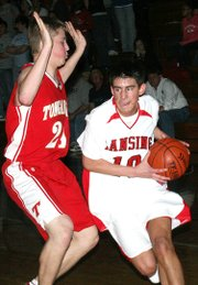 Lansing High junior point guard Curtis Beall drives to the basket during Lansing's 49-43 victory over Tonganoxie.