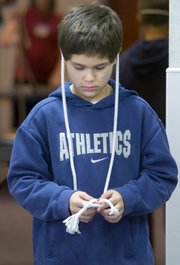Ten-year-old Wayne Regan of Shawnee had his own unique style of using his rope to practice his knot tricks during a magic class.
